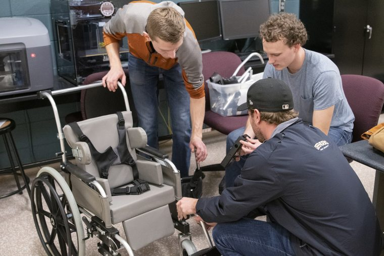Three students working on wheelchair